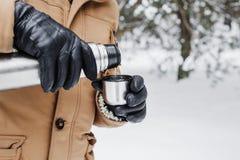 有热的饮料的人在热水瓶杯子在冬天森林里 库存图片