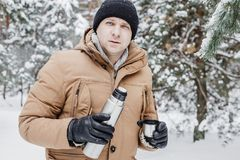有热的饮料的人在热水瓶杯子在冬天森林里 免版税图库摄影