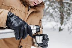 有热的饮料的人在热水瓶杯子在冬天森林里 库存照片