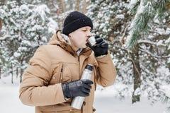 有热的饮料的人在热水瓶杯子在冬天森林里 免版税库存图片