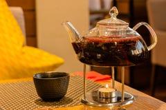 有热的饮料的茶壶在桌上的candel下 免版税库存照片