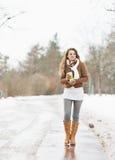 有热的饮料走在冬天公园的杯子的愉快的妇女 免版税库存照片