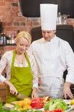 有烹调在厨房里的妇女的愉快的男性厨师厨师 免版税库存图片