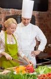 有烹调在厨房里的妇女的愉快的男性厨师厨师 免版税图库摄影