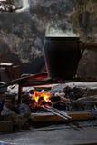 有烹调在火的午餐的罐在blackmith的车间 库存照片