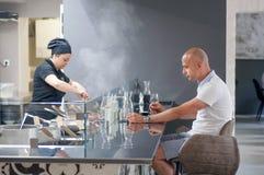 有烹调意大利食物的厨师的近顾客eationg开放厨房在现代餐馆 免版税库存图片