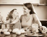 有烹调汤的孩子的妇女 免版税库存照片