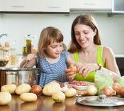 有烹调汤的孩子的愉快的母亲 库存图片