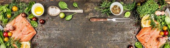 有烹调的成份未加工的三文鱼内圆角:上油,新鲜的调味料、匙子和叉子在土气木背景,顶视图,横幅 免版税图库摄影