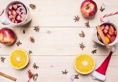 有烹调的被仔细考虑的酒两个杯子用苹果、桂香,丁香和橙色,圣诞节装饰,标示用在白色木头的框架 库存图片
