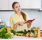 有烹饪书籍和素食者的愉快的年轻女性 图库摄影