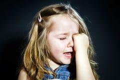 有焦点的哭泣的白肤金发的小女孩在她泪花 免版税库存图片