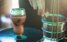 有煤炭的水烟筒碗抽烟的特写镜头的 递拿着shisha水烟筒的镊子并且调整在金属碗的热的煤炭 图库摄影