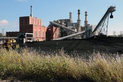 有煤炭围场和野花的一家碎煤被射击的力量厂 库存照片