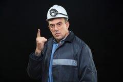 有煤矿工人帽子和安全衣物的人指向 免版税图库摄影