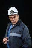 有煤矿工人帽子和安全衣物的人指向 库存照片