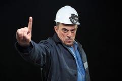 有煤矿工人帽子和安全衣物的人指向 库存图片