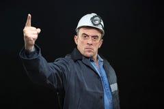 有煤矿工人帽子和安全衣物的人指向 免版税库存照片