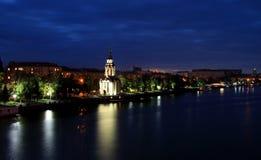 有照亮的美丽的教会在晚上,光在水中反射了 第聂伯罗彼得罗夫斯克堤防的看法,乌克兰 免版税库存图片