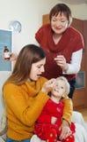 有照料病的小孩的成熟母亲的妇女 免版税图库摄影