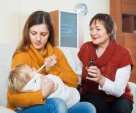有照料婴孩的成熟母亲的少妇 库存照片
