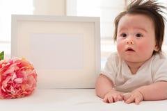 有照片框架和花的愉快的男婴 免版税库存图片