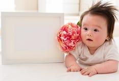 有照片框架和花的愉快的男婴 免版税图库摄影