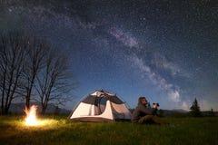 有照片照相机坐的单独近的旅游帐篷的人在营火在深蓝满天星斗的天空下 免版税图库摄影