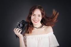 有照片照相机的与移动,吹的头发滑稽的女孩 免版税图库摄影