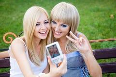 有照片照相机的二个女朋友 免版税库存照片