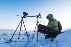 有照片照相机的人在拍timelapse照片的三脚架在北极寒带草原 库存照片