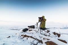 有照片照相机的人在拍timelapse照片的三脚架在北极寒带草原 免版税库存图片