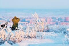 有照片照相机的人在拍timelapse照片的三脚架在北极寒带草原 库存图片