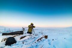有照片照相机的人在拍timelapse照片的三脚架在北极寒带草原 免版税库存照片