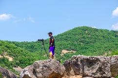 有照片照相机的男性摄影师在三脚架在石头站立我 库存图片