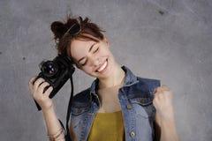 有照片照相机的滑稽的年轻和时髦行家女孩激动 免版税库存图片