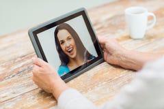 有照片的资深妇女在片剂个人计算机在家 免版税库存图片
