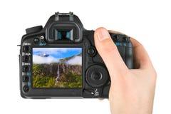 有照相机和挪威旅行照片的手 库存照片
