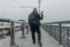 有照相机和背包的旅客摄影师沿桥梁走 查出的背面图白色 图库摄影