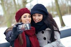 有照相机电话的两名美丽的妇女在公园 库存照片