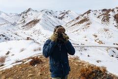 有照相机的一个快乐的旅客在哈萨克斯坦中积雪覆盖的山站立 库存照片