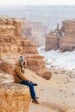 有照相机的一个快乐的旅客坐在Charyn峡谷的峭壁边缘在哈萨克斯坦 库存照片
