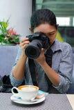 有照相机的一名妇女拍摄在餐馆的 库存图片
