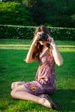 有照相机的女孩在公园 免版税库存图片