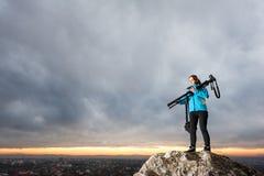 有照相机的女性摄影师在大岩石的三脚架 免版税库存图片