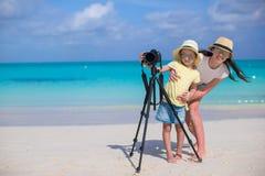有照相机的小女孩和海滩的年轻母亲 免版税图库摄影