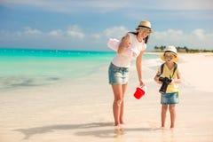 有照相机的小女孩和走在海滩的年轻母亲 库存照片