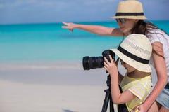 有照相机的小女孩和年轻母亲射击环境美化 库存图片