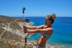 有照相机的少妇在地中海海岸 库存图片