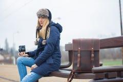 有照相机的少妇坐长凳 免版税库存图片